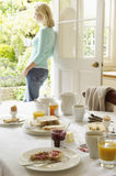 Breakfast Table With Woman In Background Stock Photo