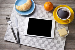 Breakfast Tablet iPad. A breakfast setting with ipad tablet on the breakfast table with the coffee and croissant stock photography