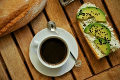 Breakfast with tea and avocado sandwich with quail eggs. Italian breakfast with tea and avocado sandwich with quail eggs  as a simple pleasure concept . Morning Stock Image