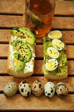 Breakfast with tea and avocado sandwich with quail eggs. Italian breakfast with tea and avocado sandwich with quail eggs  as a simple pleasure concept . Morning Royalty Free Stock Photo