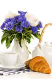 Breakfast of tea and croissant on table with blue and white bouq. Et on white background Royalty Free Stock Photography