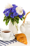 Breakfast of tea and croissant on table with blue and white bouq. Et on white background Stock Images