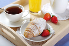 Breakfast with tea and croissants. In a wooden tray on table Royalty Free Stock Photography