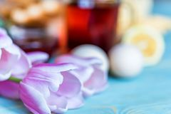 Breakfast with tea, jam and flowers. Close up table with delicious tea, toasts, boiled eggs, cheese, strawberry jam and tulips. Romantic breakfast concept Royalty Free Stock Photography
