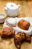 Breakfast with tea, milk and brioches. Breakfast with tea, milk , croissant and brioches on wooden board Royalty Free Stock Photography