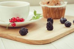 Breakfast: tea with mint, cake and fresh berries/healthy breakfast: tea with mint, cake and fresh berries on a wooden surface. Cup brunch food background table stock photography