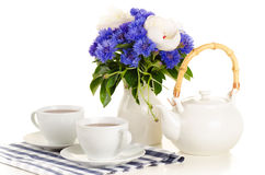 Breakfast tea on table with blue and white bouquet on white back. Ground Royalty Free Stock Photography