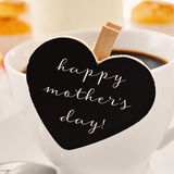 Breakfast and text happy mothers day in a heart-shaped blackboar. The sentence happy mothers day written in a heart-shaped blackboard placed in a cup of coffee Royalty Free Stock Image