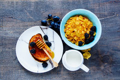 Breakfast theme table. Breakfast theme with corn flakes, grilled toasts, milk, honey, grapes and fresh blackberries on vintage wooden background. Top view. Flat stock images