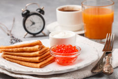 Breakfast. Thin pancakes with red caviar in white bowl. On the table. Crepes. Coffee and juice. Selective focus Royalty Free Stock Photo