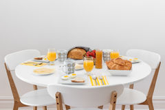 Breakfast for three. Simple tasty morning meal on a white table Royalty Free Stock Photos