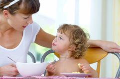 Breakfast time. Portrait of young woman feeding her baby daughter Royalty Free Stock Image