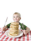 Breakfast Time. Young boy with a giant plate of pancakes, a knife and fork on a table cloth. Shallow DOF with focus on the pancakes royalty free stock photos
