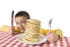 Breakfast Time. Young boy with a giant plate of pancakes, a knife and fork on a table cloth. Shallow DOF with focus on the pancakes Stock Photo
