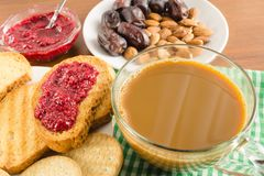 Breakfast time, cup of coffee with milk, toasts, raspberry jam, dates, almonds at napkin on wooden table. Breakfast time, cup of coffee with milk, toasts Royalty Free Stock Photos