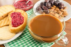 Breakfast time, cup of coffee with milk, toasts, raspberry jam, dates, almonds at napkin on wooden table. Breakfast time, cup of coffee with milk, toasts Royalty Free Stock Images