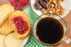Breakfast time, cup of coffee with toasts, raspberry jam, dates, almonds at napkin on wooden table. Breakfast time, cup of coffee with toasts, raspberry jam Stock Photos