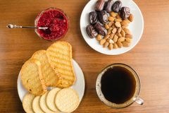 Breakfast time, cup of coffee with toasts, raspberry jam, dates, almonds on wooden table, top view. Breakfast time, cup of coffee with toasts, raspberry jam Stock Photo