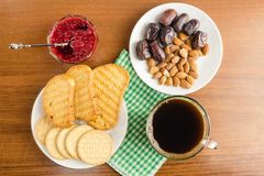 Breakfast time, cup of coffee with toasts, raspberry jam, dates, almonds on wooden table, top view. Breakfast time, cup of coffee with toasts, raspberry jam Royalty Free Stock Image