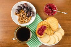 Breakfast time, cup of coffee with toasts, raspberry jam, dates, almonds on wooden table, top view. Breakfast time, cup of coffee with toasts, raspberry jam Stock Photos