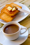 Breakfast time: cup of milky coffee, rusks with butter and jam Royalty Free Stock Images