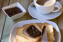 Breakfast time: cup of milky coffee, rusks and chestnuts cream Royalty Free Stock Photography