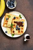 Breakfast time. Homemade waffles with banana, blueberry and chocolate spread on a kitchen table. Breakfast time. Homemade waffles with banana, blueberry and stock photography