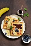 Breakfast time. Homemade waffles with banana, blueberry and chocolate spread on a kitchen table. Breakfast time. Homemade waffles with banana, blueberry and stock photos