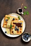 Breakfast time. Homemade waffles with banana, blueberry and chocolate spread on a kitchen table. Breakfast time. Homemade waffles with banana, blueberry and royalty free stock photography