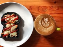Breakfast time, Mini pizza made by charcoal bread and latte art coffee on the wooden table stock photos