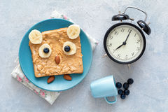 Breakfast time: peanut butter sandwich and clock Royalty Free Stock Photo