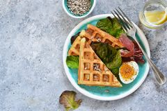 Breakfast time. Waffle with prosciutto, salad and egg for breakfast on a concrete background. View from above royalty free stock photos