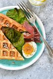 Breakfast time. Waffle with prosciutto, salad and egg for breakfast on a concrete background. View from above royalty free stock photo