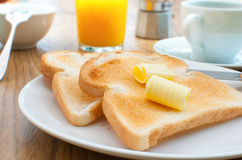 Breakfast toast and coffee. Breakfast table with butter on toast and a coffee cup in the background Stock Photos