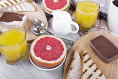 Breakfast with toast and fruit. Breakfast with coffee and orange juice, grapefruit, toast and chocolate spread Stock Photos