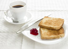 Breakfast with toast,marmalade and coffee. Delicious breakfast with toast,raspberry marmalade and coffee.Morning sunlight.White dishes and tablecloth Royalty Free Stock Photography