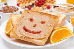 Breakfast - toast with peanut butter and drawing of jam. Close-up Royalty Free Stock Images