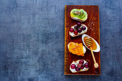 Breakfast toast pieces. Top view of healthy breakfast toast pieces set. Wholegrain baguette slices with cream cheese, various fruit, honey, seeds and nuts. Slate Stock Photography