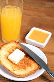 Breakfast: toasts with butter, juice and orange jam Royalty Free Stock Photos
