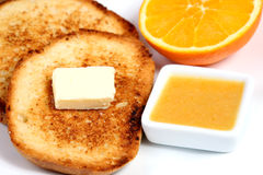 Breakfast: toasts with butter, orange and orange jam Stock Image