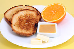 Breakfast: toasts with butter, orange and orange jam on yellow background Stock Images