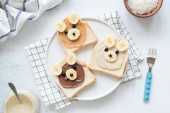 Breakfast toasts with nut butter and banana with cute funny animal face. Kids food. Breakfast for kids or school lunch. Top view stock image