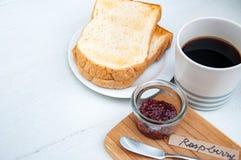 Breakfast: toasts, raspberry jam, cup of black coffee Stock Photography