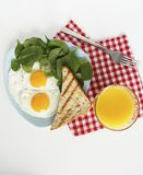 Breakfast. top view. eggs, orange juice, spinach, toasts royalty free stock image