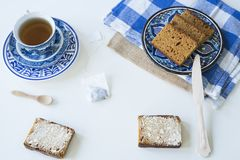Breakfast with traditional Dutch spiced caked called ontbijtkoek or peperkoek. cup of tea, white background stock photography