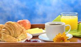 Breakfast on Tray. Delicious breakfast on tray consisting of coffee, orange juice, apple, croissants, jam and butter (Selective Focus, Focus on the front Royalty Free Stock Image