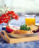 Breakfast Tray. Beautiful breakfast tray with juice, toast and tomatoes on a blue spread with flowers Royalty Free Stock Photography