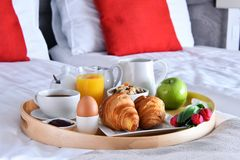 Breakfast on tray in bed in hotel room.  Royalty Free Stock Photos