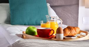 Breakfast on tray in bed in hotel room.  Stock Images