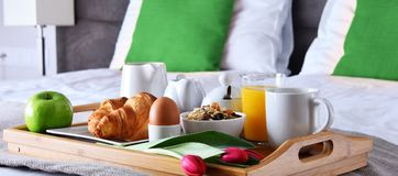 Breakfast on tray in bed in hotel room.  Royalty Free Stock Image